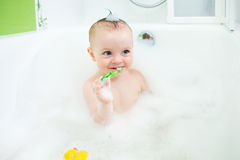 Baby brushing teeth in bathroom Royalty Free Stock Images