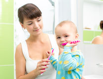 Baby brushing teeth in bathroom Royalty Free Stock Image