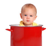 Baby in a Bucket. A baby sitting in a red cooking pot Stock Image