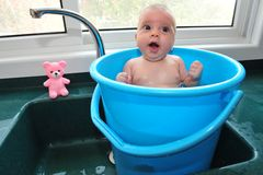 Baby in a Bucket. A baby in a blue bucket cools off in the summer heat Royalty Free Stock Photography