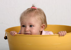Baby in a bucket. Baby peering over the side of a yellow can or bucket Stock Photos