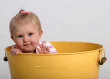 Baby in a bucket. Baby inside a yellow can or bucket Stock Images