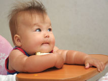 Baby in the bucket seat holding food Royalty Free Stock Photo