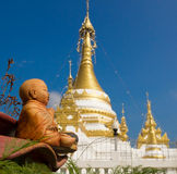 Baby Buddha statue against the Stupa Stock Image
