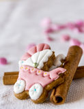 Baby buggy cookies for princesses with cinnamon. Baby buggy ginger cookies placed on a cinnamon on a white background with pink decorations Royalty Free Stock Image
