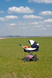 A baby buggy standing alone in the fields Stock Photo