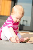 Baby building. Baby sitting on a deck outside, exploring her feet and hands stock photo