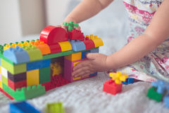 Baby builds house from designer, close-up, real Royalty Free Stock Photos