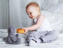 Baby with a bun. Baby in bed at home with a bun royalty free stock image