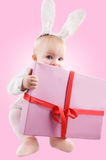 Baby in bunny costume with present Stock Image