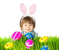 Baby with bunny ears and easter eggs. Portrait of adorable baby with bunny ears and colorful easter eggs in the grass. Studio shot, isolated, on a white Stock Photography