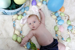 Baby with bunny ears on an Easter Set Stock Image