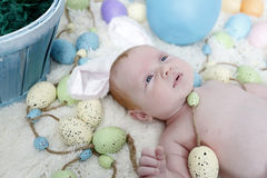 Baby with bunny ears on an Easter Set Stock Photo