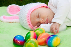 Baby in a bunny hat with Easter Eggs. Adorable sleeping newborn baby in a bunny hat with a pile of colorful Easter Eggs to celebrate the season, close up of the Royalty Free Stock Images