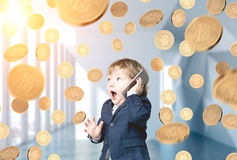 Baby businessman and bitcoin rain. Portrait of a cute blond baby boy talking on a smartphone and being surprised. He is standing in an office lobby under a Stock Photo