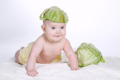 Baby with cabbage leaf on his head royalty free stock photos