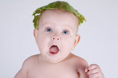 Baby with cabbage leaf on his head stock photography