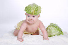 Baby with cabbage leaf on his head. Cute baby with cabbage leaf on his head Stock Image