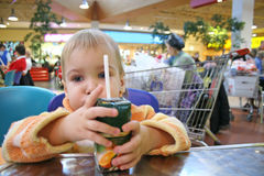 Baby in cafe. Baby with juice in cafe Stock Images