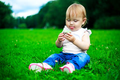 Baby with a cake. Baby eating a cake outdoor in the summer park Royalty Free Stock Photo