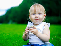 Baby with a cake. Baby eating a cake outdoor in the summer park Royalty Free Stock Images