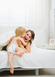 Baby came to mother in bedroom Stock Photography