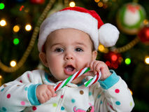 Baby with a Candy cane. Serious Baby in a Christmas hat with a Candy Cane stock images