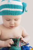 The baby in a cap plays with a green one shoe Royalty Free Stock Photos