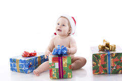 Baby in a cap of Santa Claus with gifts Stock Photos
