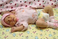 Baby in cap sleeps. On the diaper Stock Images