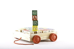 Baby car. Kids wooden alphabet letter set in a wooden box with wheels with cubes spelling the word baby Royalty Free Stock Image