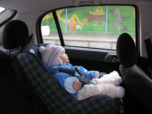 Baby in car with dreams in window stock photos