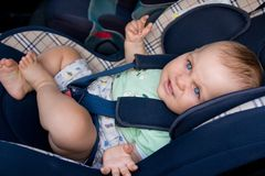 Baby in a car seat. Little baby sitting in safety car seat Royalty Free Stock Images
