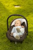Baby in car seat on grass Stock Photos