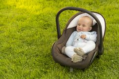 Baby in car seat on grass Royalty Free Stock Images