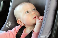 Baby in a car seat looking puzzled royalty free stock photo