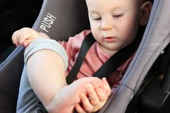 Baby in a car seat playing with her toes royalty free stock image