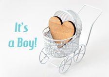 Baby card - Its a boy theme. Pram with wooden heart on white background. Newborn greeting card. Baby card - Its a boy theme. Pram with wooden heart on white Royalty Free Stock Photos
