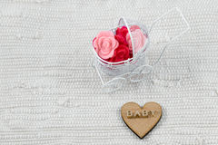 Baby card - Its a girl theme. Golden letters. Word baby on wood. Pram full of flowers on white textile background. Newborn greetin Royalty Free Stock Photo
