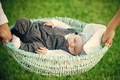 Baby care. Baby boy sleep in crib held in hands. Child son asleep in basket on green grass. Dream, bedtime, nap. Comfort, relax, tranquility. Family, love stock photography