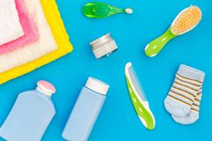 Baby care. Bath cosmetics and accessories for child. Shampoo, gel, cream, towel, brush on blue background top view stock photo