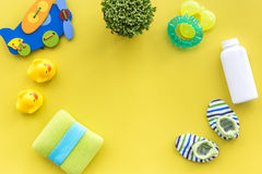 Baby care with bath set, ducklings and towel on yellow background top view mockup