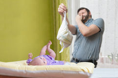 Baby care concept. Father od dad is changing stinky diaper Royalty Free Stock Photo
