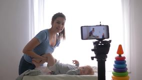 Baby care, happy blogger mama changes clothes of child boy while recording training video on mobile telephone for. Subscribers in social networks in streaming stock footage