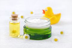 Baby care products, natural cream, massage oil and fresh chamomile flowers. With a duck royalty free stock photos