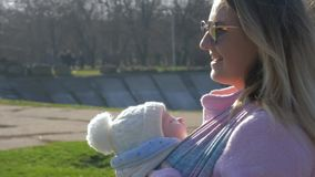 Baby care, smiling female in sunglasses with newborn walking along street. Close-up stock footage
