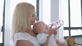 Baby care, young happy mother holds infant girl in arms and gives to drink water from bottle stock video