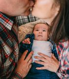 Baby carefully looks parents kissing home style stock photo