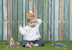 Baby with carnival hat seated in the garden Royalty Free Stock Photography