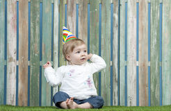Baby with carnival hat seated in the garden. Against a fence Royalty Free Stock Photography